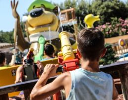 Child squirting water out of canon water ride